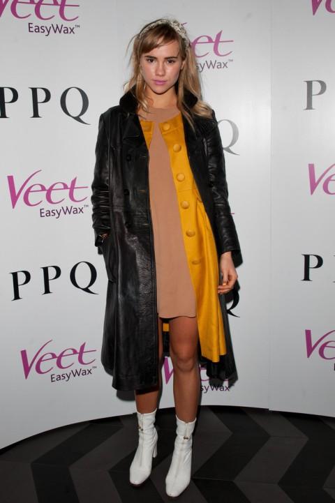 Suki Waterhouse StyleChi PPQ After Party Black Long Leather Coat Yellow Ochre Coat Nude Dress White Sixties Boots Headband