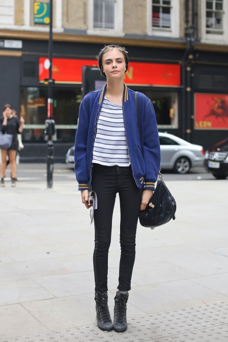 Cara Delevingne StyleChi Black Skinny Jeans Blue Orange Varsity Jacket Blue White Striped T-Shirt Hat Lace Up Wedge Trainers