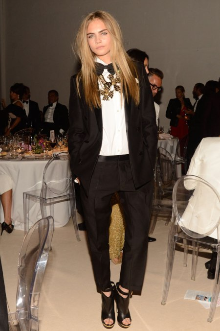 Cara Delevingne StyleChi Party Outfit Black Suit Blazer Cropped Tailored Trousers White Shirt Bow Tie Gold Statement Necklace Peep Toe Shoe Boots
